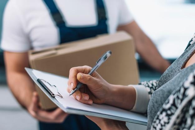 Женщина подросток подписывает на посылку
