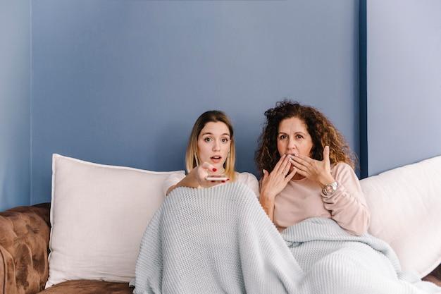 テレビを見ている驚いた女性