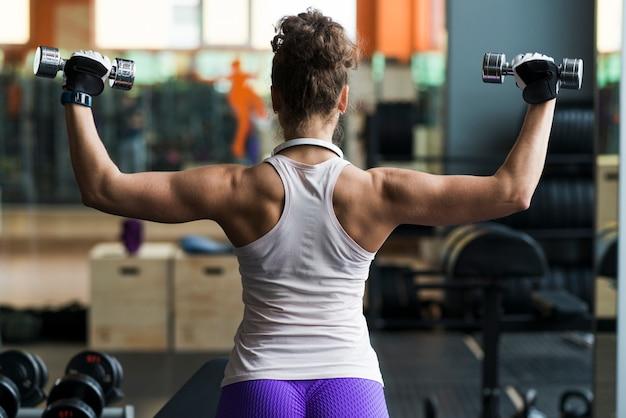 Вид сзади женщина, упражнения с гантелями