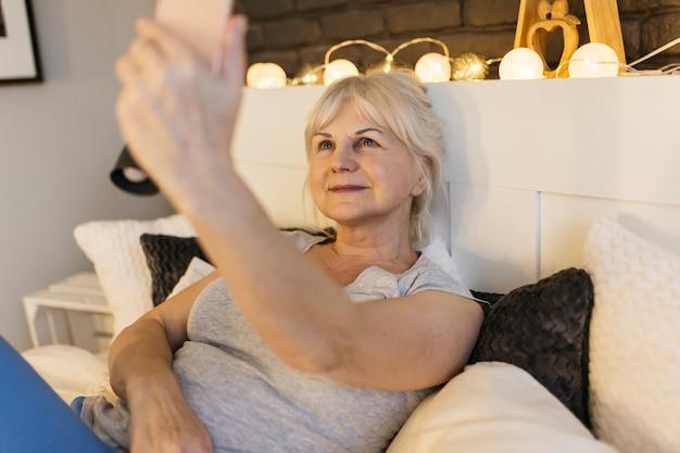 Пожилая женщина, берущая себя на кровати