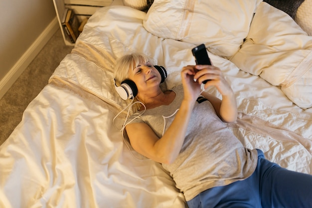 Сверху пожилая женщина слушает музыку на кровати