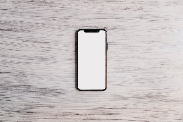 Мобильный телефон с белым белым экраном на деревянной столешнице