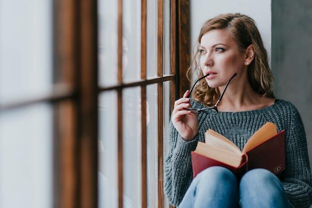 女性は、本と眼鏡を考えている