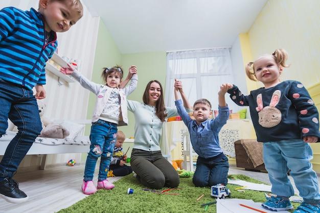 教師と子供たちが教室で遊ぶ