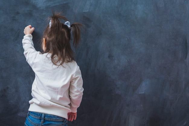 小さなブルネットの女の子が壁に書く