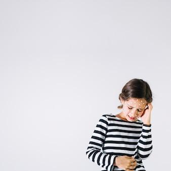 痛みに苦しむ発疹のある女の子