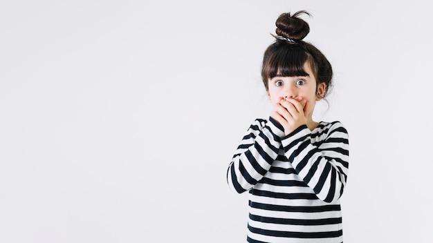 Потрясшая девушка, покрывающая рот