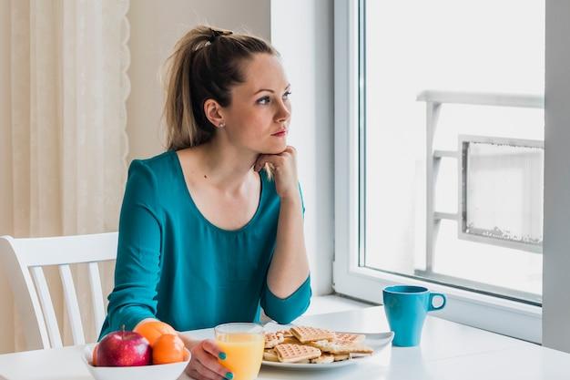 Задумчивая женщина с завтраком