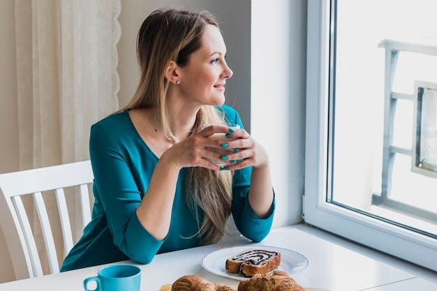 ミルクのガラスで笑顔の女性