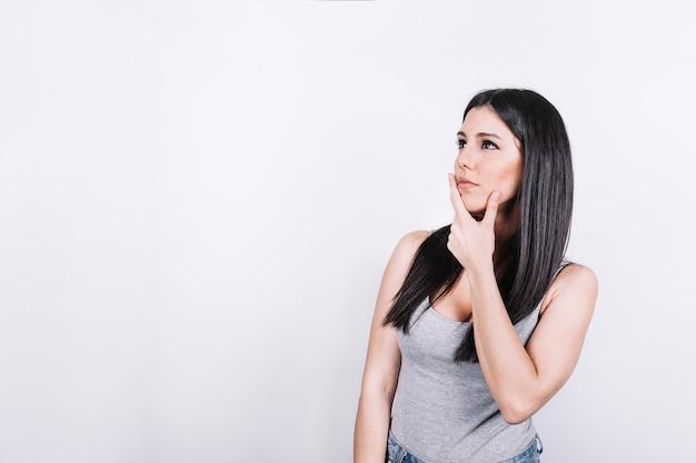 Женщина потирает подбородок и думает