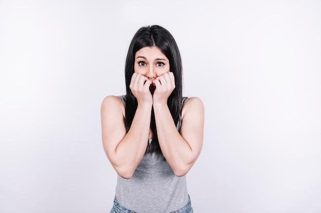 Испуганная женщина, кусающая гвозди