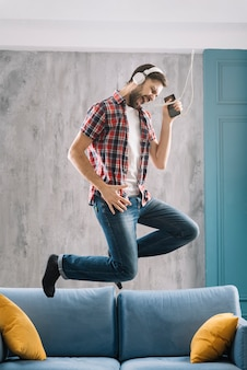 Человек слушает музыку и прыгает на диване