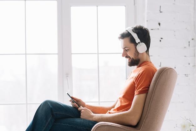 窓の近くで音楽を聴いている男