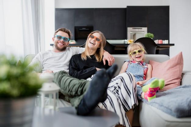 Веселая семья смотрит фильм на диване