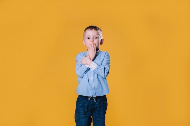Потрясенный мальчик, покрывающий рот