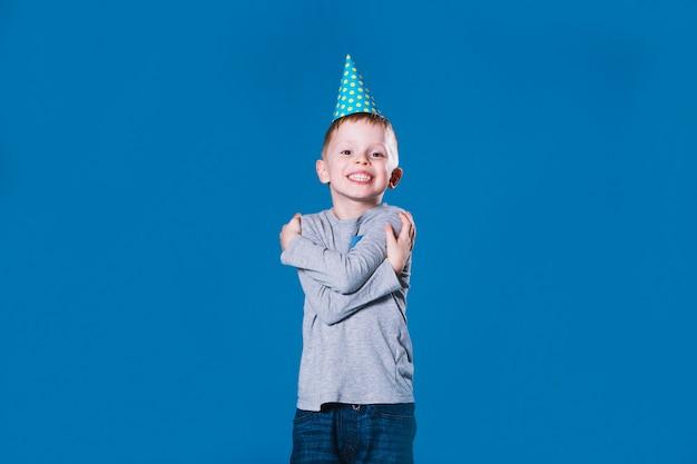 Мальчик в шляпе участника, обнимающий себя