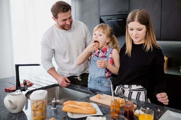 Девушка ест возле родителей