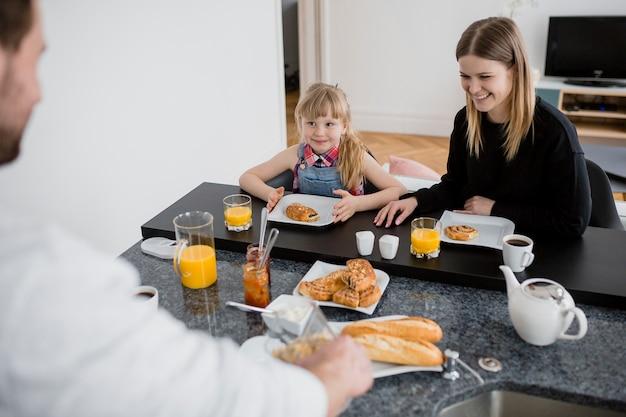 母親と娘が父親の近くで朝食を取る