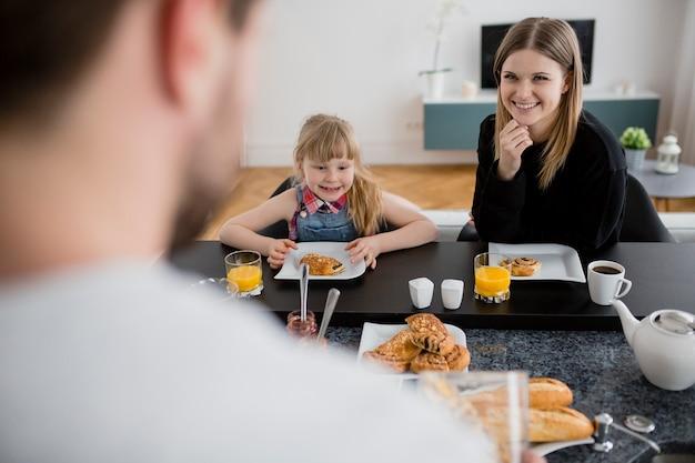 娘とお母さん、朝食中の父親を見て