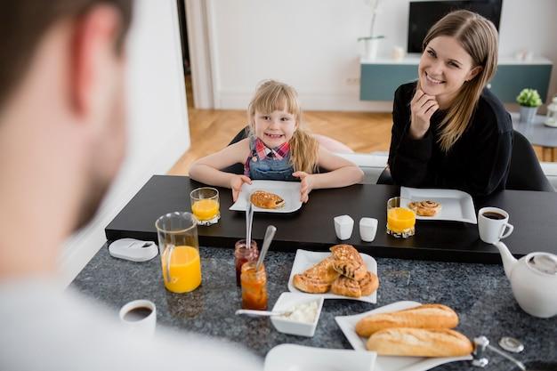 母親と娘の近くのお父さんは朝食を取る