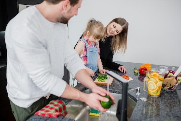 Отец смотрит на дочь и жену резки овощей