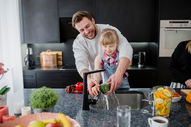 朗らかな父親と娘の野菜を洗浄する
