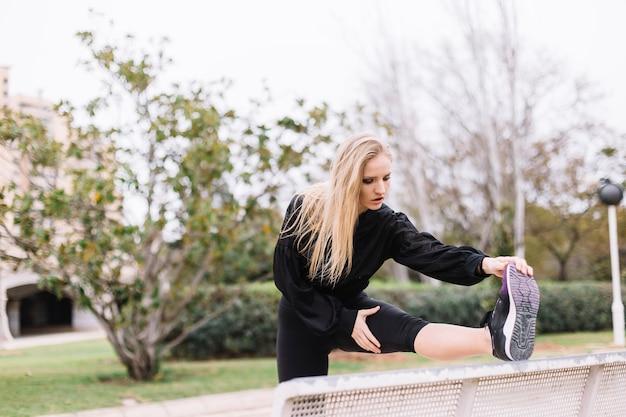 Женщина, растягивая ноги на улице