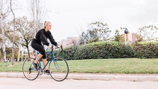 公園に乗って素敵な女性が乗る自転車