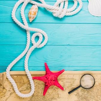 Крупный план веревки рядом с морскими звездами и картами