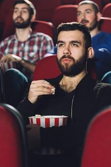 映画館でポップコーンを食べている男