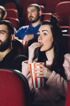 Красивая женщина есть попкорн в кино