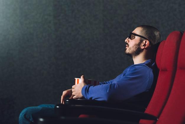 映画館で映画を楽しむ男