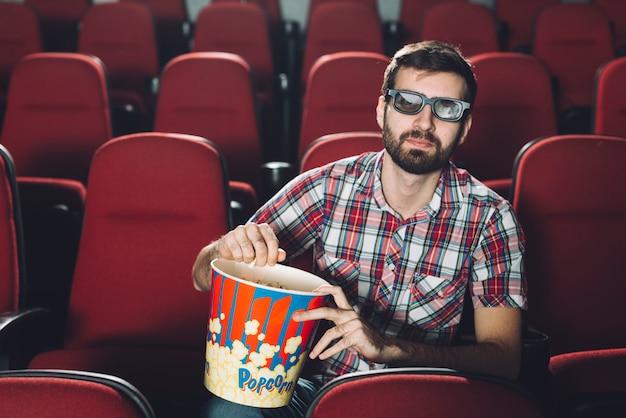 映画の中でポップコーンを食べるハンサムな男