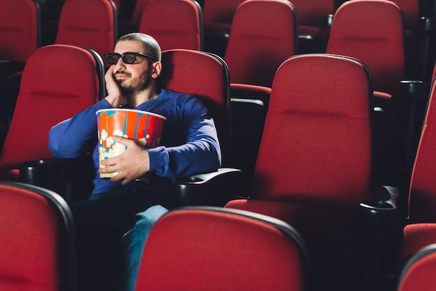 映画館で映画を見ている退屈な男