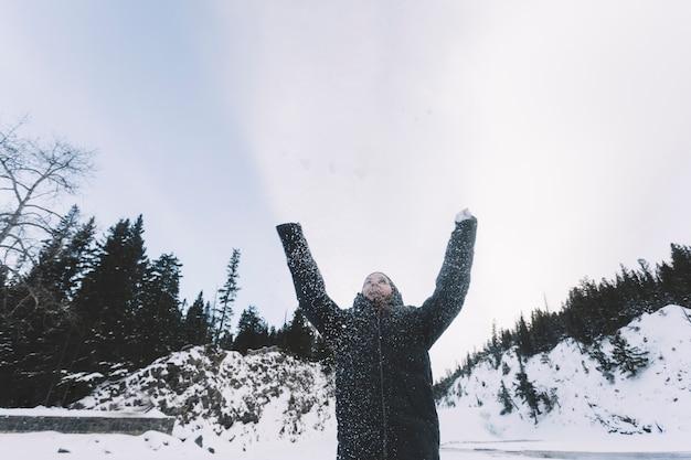 森林の背景に雪を投げる人