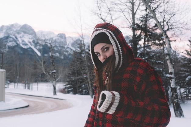 自然の背景に暖かいジャケットの女性
