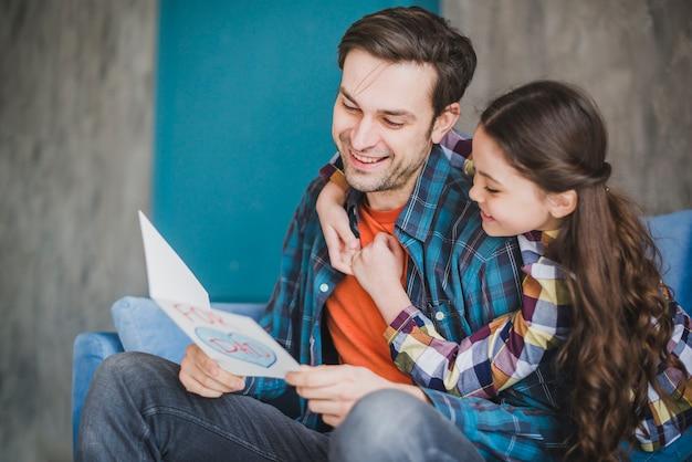 Счастливый отец и дочь, глядя на руку обращается карты в отцовский день