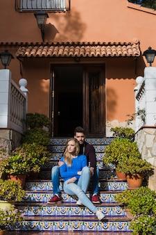 Молодая пара, сидя на крыльце
