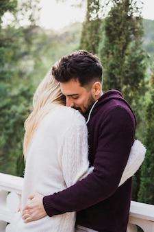 抱擁で立っている恋人のカップル