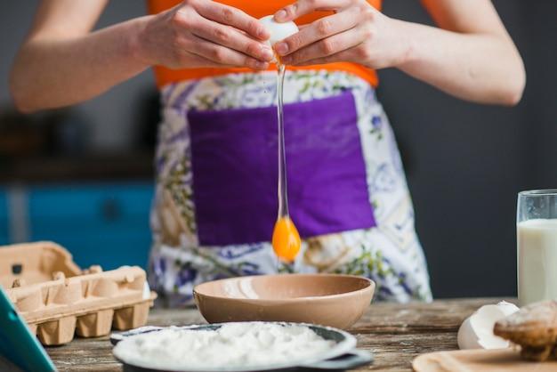 作物の女性が卵をボウルに割る