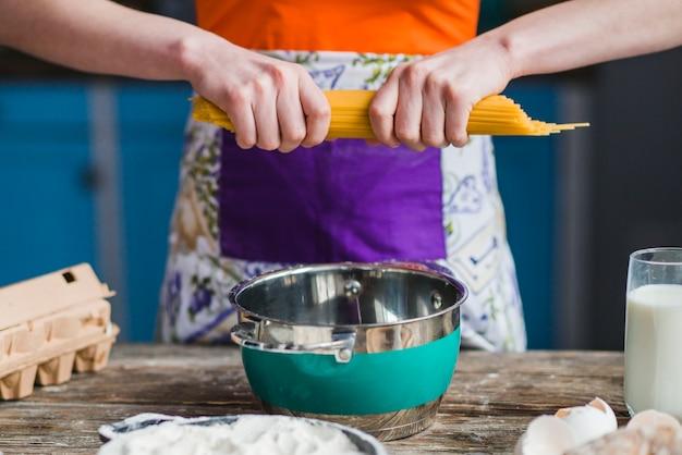 鍋の上にスパゲッティを割る作物の女性