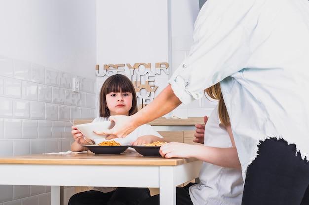 Мать, приносящая еду для дочерей на столе