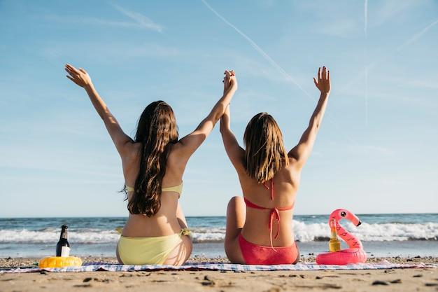 ビーチに座っている楽しい女性のバックビュー