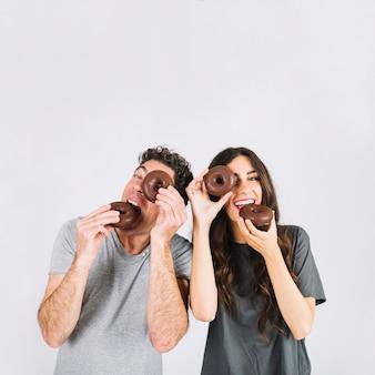 Отец и дочь едят пончики