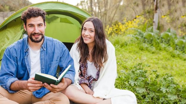 Пара читает возле палатки