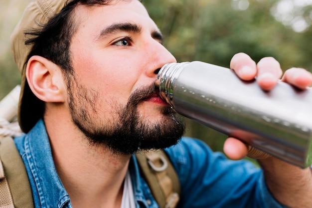 Человек, пьющий из термос