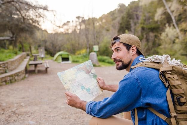 自然の中の地図を持つツーリスト