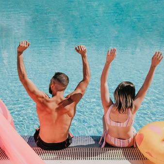 Пара, поднимающая оружие рядом с бассейном