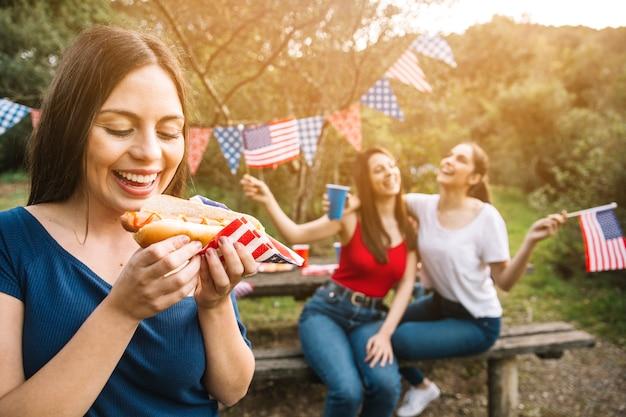 ホットドッグを食べる女性