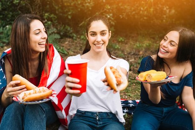 ホットドッグとドリンクを提案する若い女性